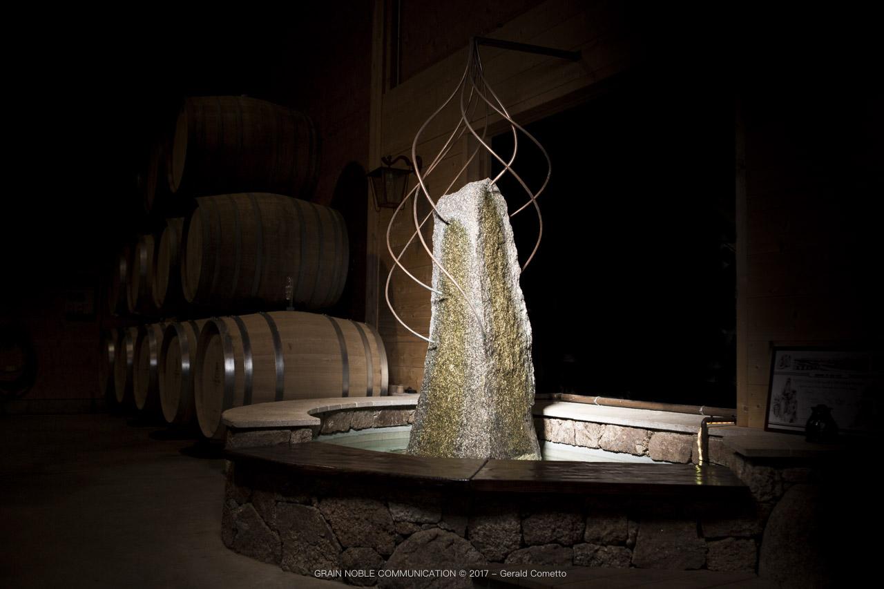 photo d'un menhir entouré d'eau et de 7 fils en cuivre