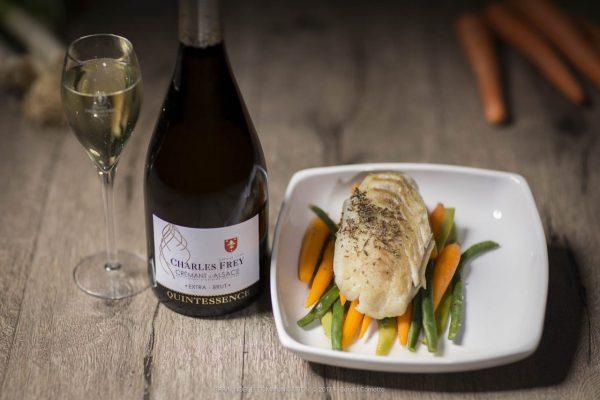 photo d'une bouteille de Crémant d'Alsace avec un plat de poisson