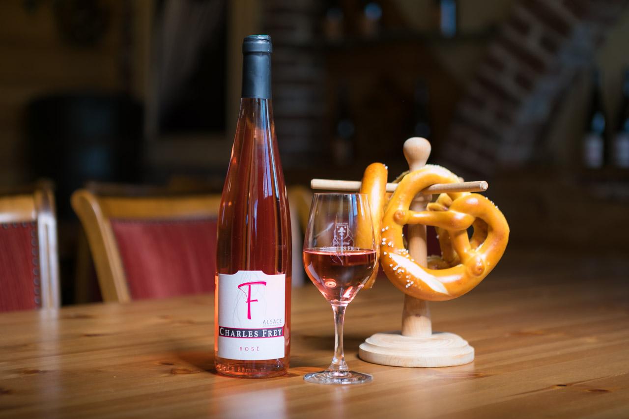 photo d'une bouteille de vin rosé avec un verre rempli et des bretzels en fond