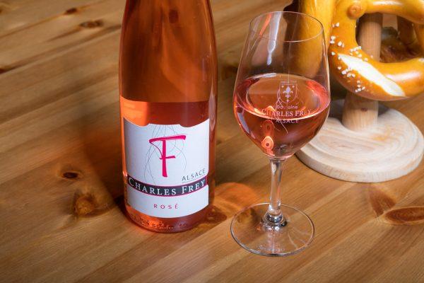 photo d'une bouteille de vin rosé avec un verre plein et un bretzel
